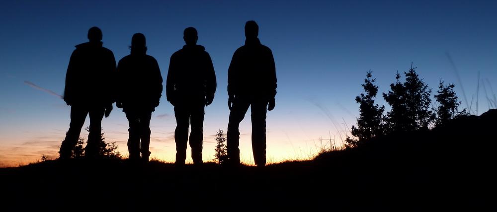 Vier finstere Gestalten warten auf den Sonnenaufgang