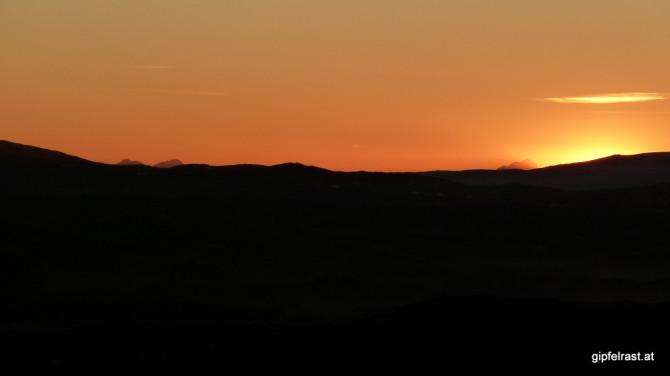 Seltene Gipfel: Die Sonne versinkt neben dem slowenisch-kärntner Dreigestirn aus Vertatscha, Hochstuhl und Triglav.